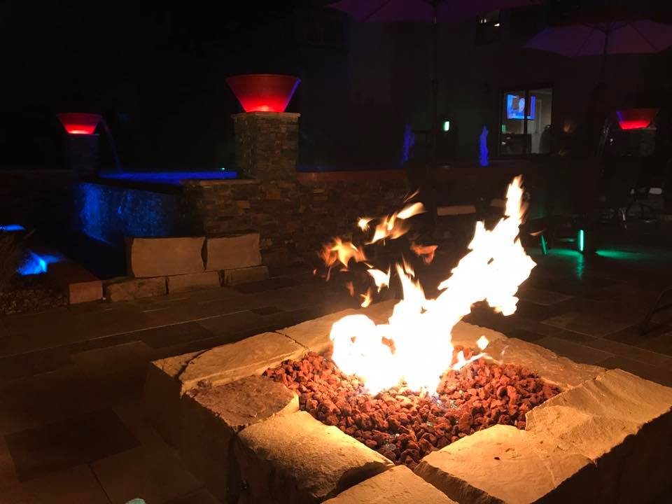 Fire Pit Blazing at night in a back yard for outdoor living and entertaining.
